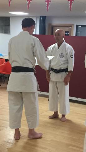 Tim Shaw is presented with his 7th Dan certificate from Sugasawa Sensei.